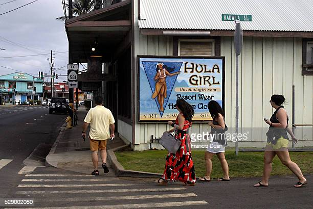 Kauai island visitors walk by the Hula Girl billbard at kapa'a park kauwila street where all shops are closed to due to new year holiday 1 Jan 2013