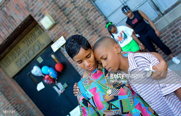 Kawana Roberts and her son Kayon bow their heads during a moment of silence for RB singer Aaliyah Haughton August 27 2001 at a memorial candlelight...