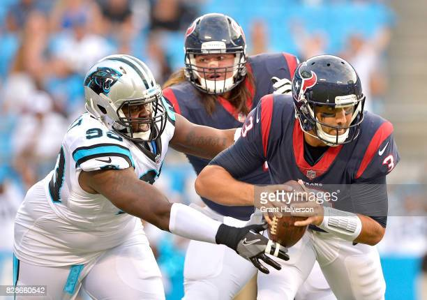 Kawann Short of the Carolina Panthers pressures Tom Savage of the Houston Texans during the preseason at Bank of America Stadium on August 9 2017 in...