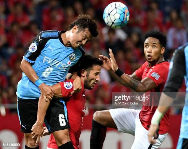 Kawasaki Frontale midfielder Yusuke Tasaka fights for the ball with Urawa Reds forward Zlatan during the AFC Champions League quarter final match...
