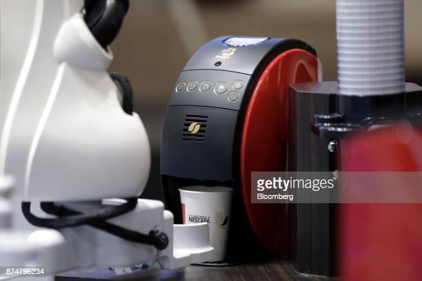 A Kawasaki Heavy Industries Ltd dualarm SCARA robot known as 'duAro' sets a cup on a Nestle SA Nescafe Gold Blend Barista 50 coffee machine during a...