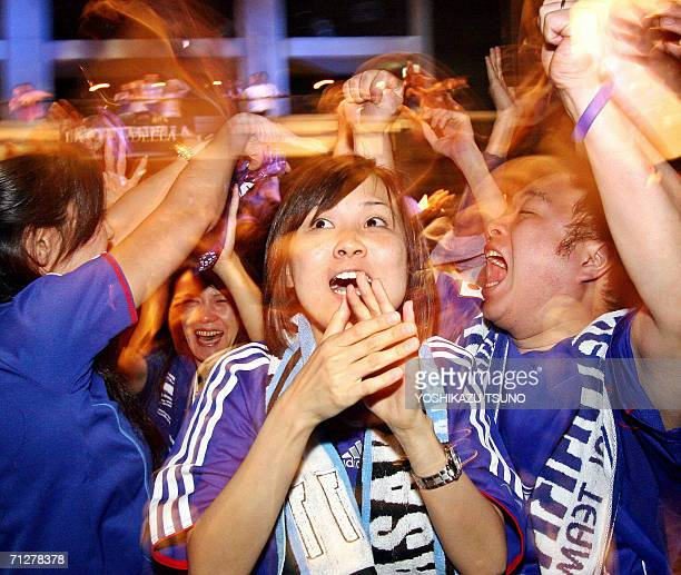 Japanese football fans celebrate Japan's first goal during a public viewing of the live broadcasting of the FIFA World Cup 2006 at Kawasaki suburban...