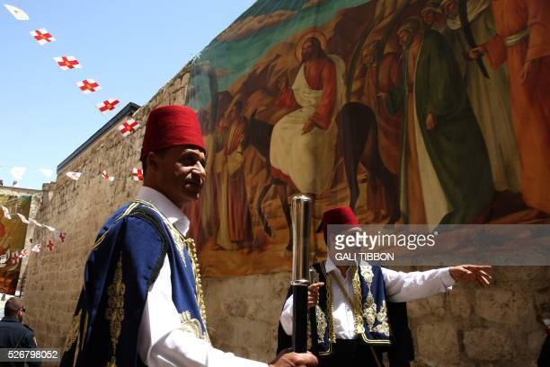 Kawases of the Greek Orthodox patriarchate in traditional Ottoman outfits walk past Easter decorations as they head to the Church of the Holy...