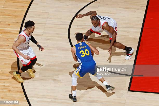 Kawhi Leonard and Danny Green of the Toronto Raptors guard Stephen Curry of the Golden State Warriors during Game Five of the NBA Finals on June 10...
