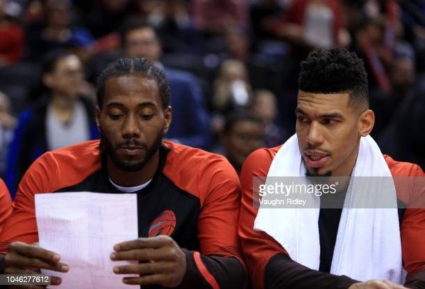 Kawhi Leonard and Danny Green of the Toronto Raptors sit on the bench reading the half time stats during the second half of an NBA preseason game...