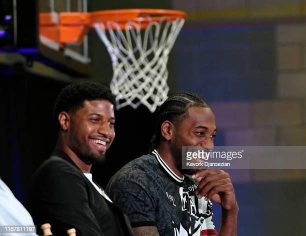 Kawhi Leonard and Paul George laugh as they listen to Los Angeles Clippers owner Steve Ballmer speak during their introductory news conference at...
