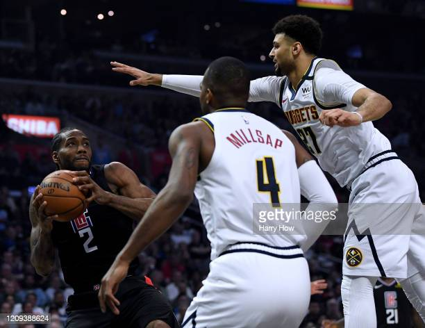 Kawhi Leonard of the LA Clippers attempts a shot in front of Jamal Murray and Paul Millsap of the Denver Nuggets during the first half at Staples...