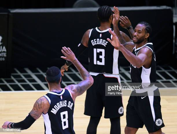 Kawhi Leonard of the LA Clippers celebrates is basket off of a Clipper free throw, with Paul George and Marcus Morris Sr. #8, to end the third...