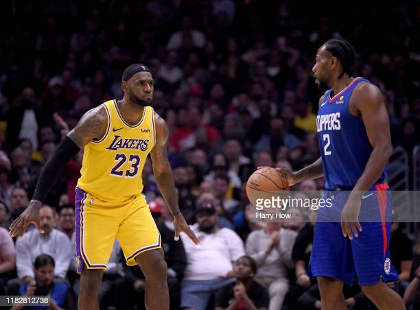 Kawhi Leonard of the LA Clippers controls possession of the ball in front of LeBron James of the Los Angeles Lakers late in the fourth quarter in a...