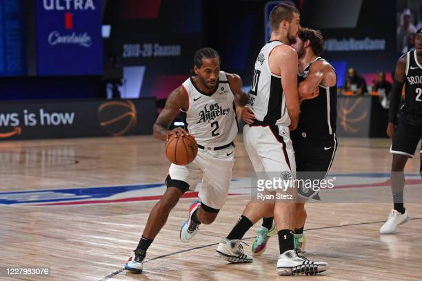 Kawhi Leonard of the LA Clippers dribbles the ball around a screen against the Brooklyn Nets on August 9 2020 in Orlando Florida at AdventHealth...