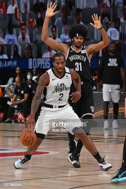 Kawhi Leonard of the LA Clippers dribbles the ball up court while guarded by Jarrett Allen of the Brooklyn Nets on August 9 2020 in Orlando Florida...