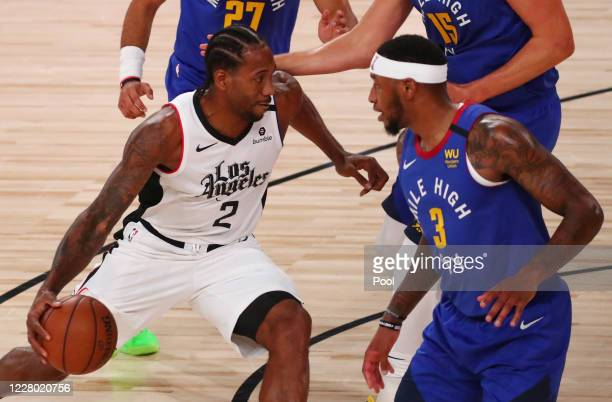 Kawhi Leonard of the LA Clippers drives to the basket against Torrey Craig of the Denver Nuggets in the first quarter at AdventHealth Arena at ESPN...