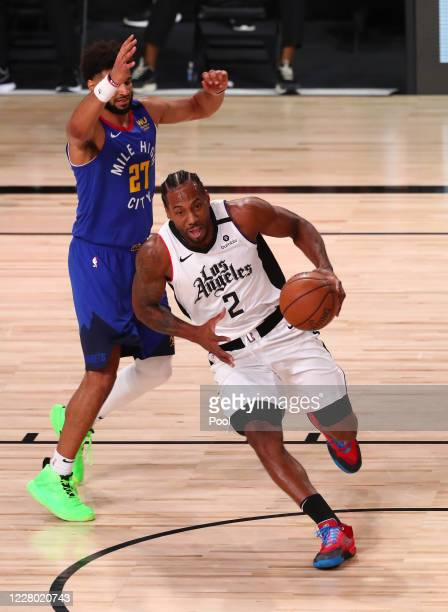 Kawhi Leonard of the LA Clippers drives to the basket past Jamal Murray of the Denver Nuggets in the first quarter at AdventHealth Arena at ESPN Wide...