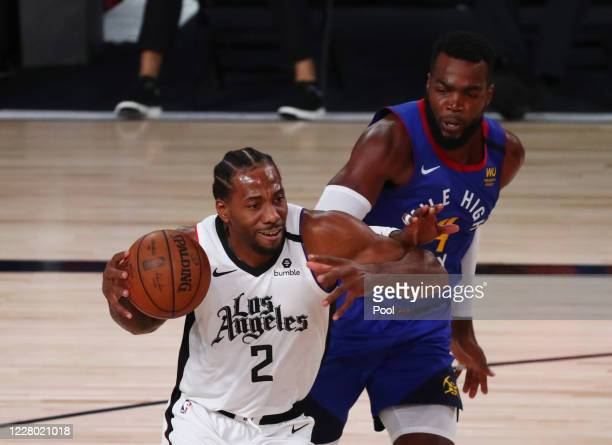 Kawhi Leonard of the LA Clippers drives to the basket past Paul Millsap of the Denver Nuggets in the second quarter at AdventHealth Arena at ESPN...