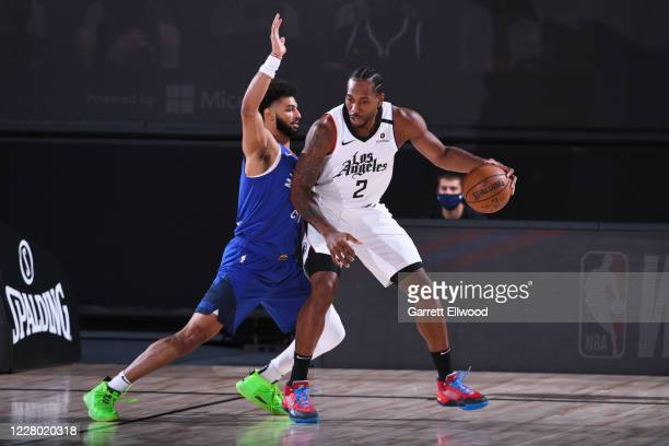 Kawhi Leonard of the LA Clippers handles the ball against Jamal Murray of the Denver Nuggets on August 12 2020 at the AdventHealth Arena at in...