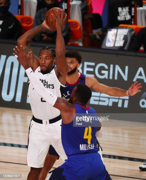 Kawhi Leonard of the LA Clippers is defended by Paul Millsap and Jamal Murray of the Denver Nuggets in the third quarter at AdventHealth Arena at...