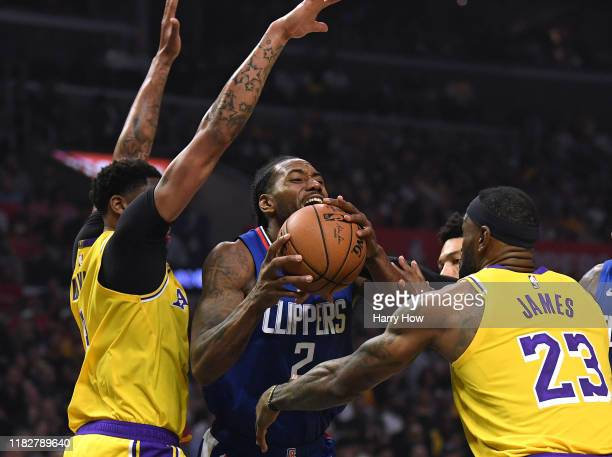 Kawhi Leonard of the LA Clippers is fouled by LeBron James of the Los Angeles Lakers as he steps by Anthony Davis during the first half in the LA...