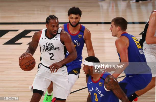Kawhi Leonard of the LA Clippers is guarded by Nikola Jokic of the Denver Nuggets in the first quarter at AdventHealth Arena at ESPN Wide World Of...
