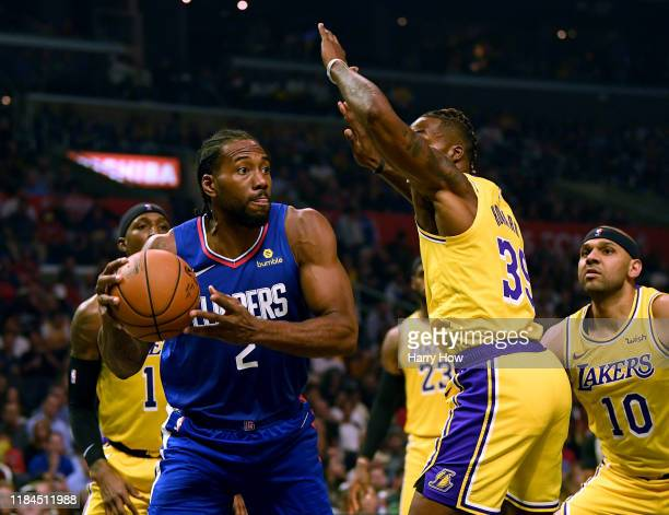 Kawhi Leonard of the LA Clippers looks to pass around Dwight Howard and Jared Dudley of the Los Angeles Lakers during the LA Clippers season home...