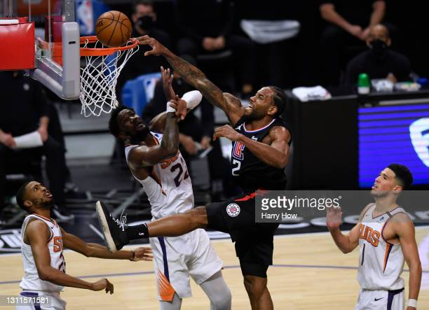 Kawhi Leonard of the LA Clippers reacts as he dunks over Deandre Ayton of the Phoenix Suns during the third quarter at Staples Center on April 08,...