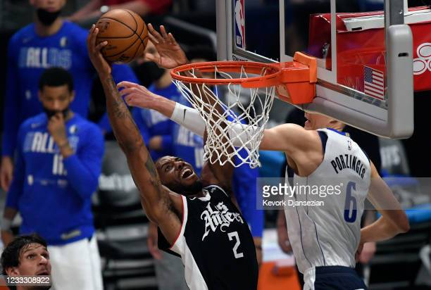Kawhi Leonard of the Los Angeles Clippers dunks the ball against Kristaps Porzingis of the Dallas Mavericks during the second half of Game Seven of...