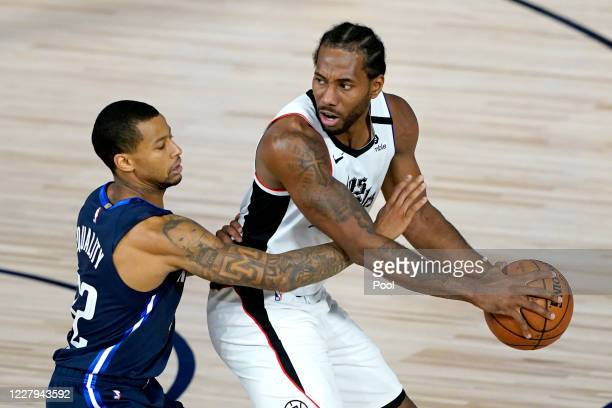 Kawhi Leonard of the Los Angeles Clippers is guarded by Trey Burke of the Dallas Mavericks during the second half of an NBA basketball game at the...