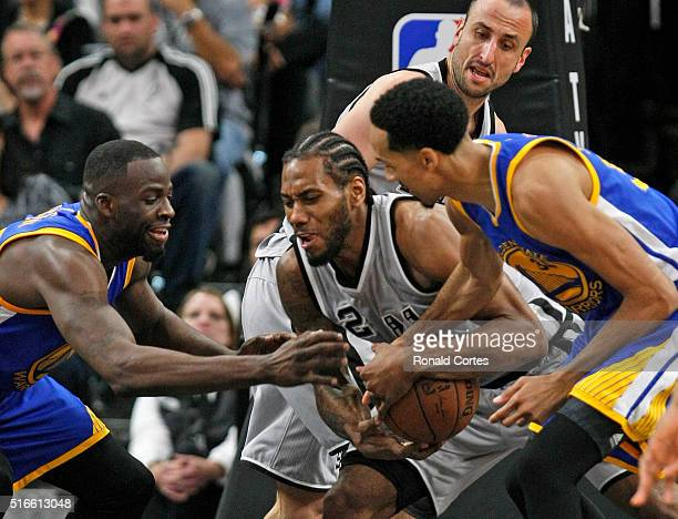 Kawhi Leonard of the San Antonio Spurs battles Draymond Green of the Golden States Warriors and Shaun Livingston of the Golden States Warriors for a...