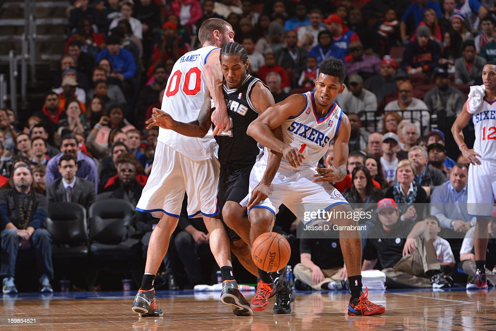 Kawhi Leonard #2 of the San Antonio Spurs battles for a loose ball against Nick Young #1 of the Philadelphia 76ers during the game at the Wells Fargo Center on January 21, 2013 in Philadelphia, Pennsylvania.