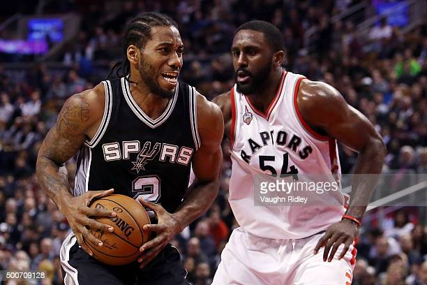 Kawhi Leonard of the San Antonio Spurs battles with Patrick Patterson of the Toronto Raptors during an NBA game at the Air Canada Centre on December...