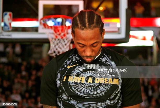 Kawhi Leonard of the San Antonio Spurs bows his head during the playing of the National Anthem before the start of his game against the Denver...