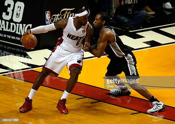 Kawhi Leonard of the San Antonio Spurs defends against LeBron James of the Miami Heat during Game Three of the 2014 NBA Finals at American Airlines...