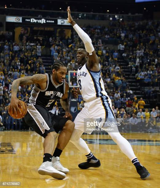 Kawhi Leonard of the San Antonio Spurs dribbles behind his back past James Ennis of the Memphis Grizzlies during the second half of a 10396 Spurs...