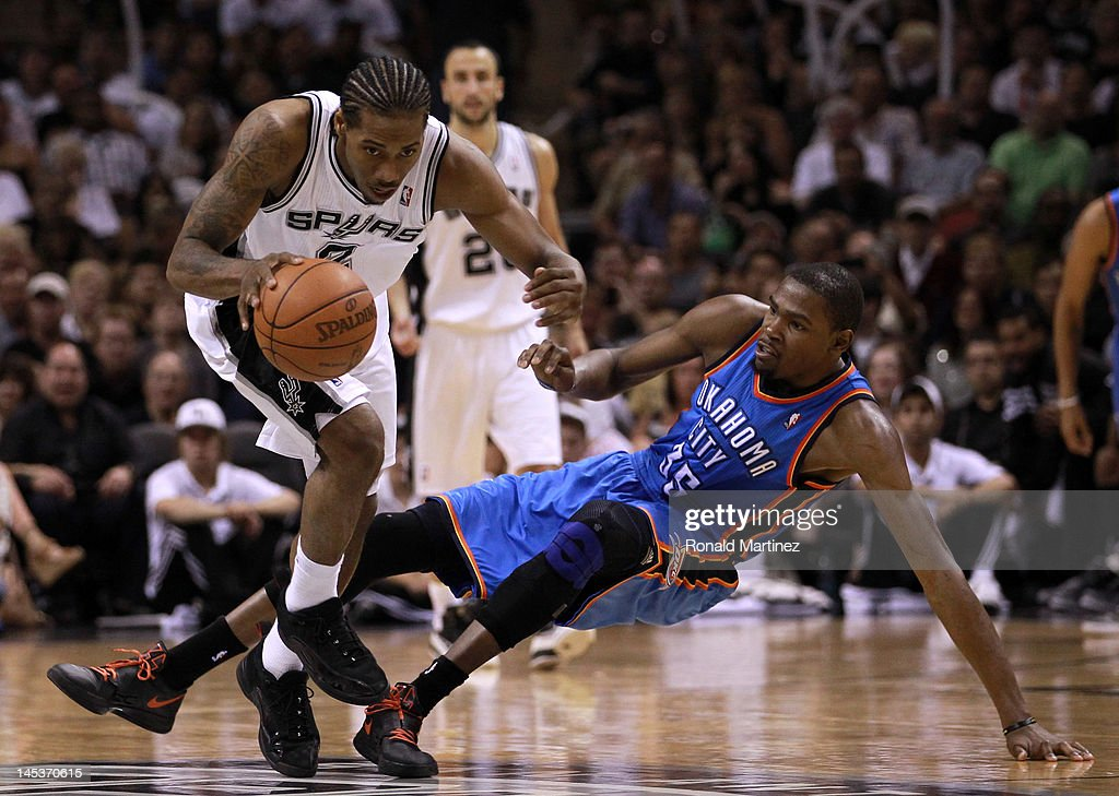 Kawhi Leonard #2 of the San Antonio Spurs dribbles the ball alongside Kevin Durant #35 of the Oklahoma City Thunder in the second half in Game One of the Western Conference Finals of the 2012 NBA Playoffs at AT&T Center on May 27, 2012 in San Antonio, Texas.