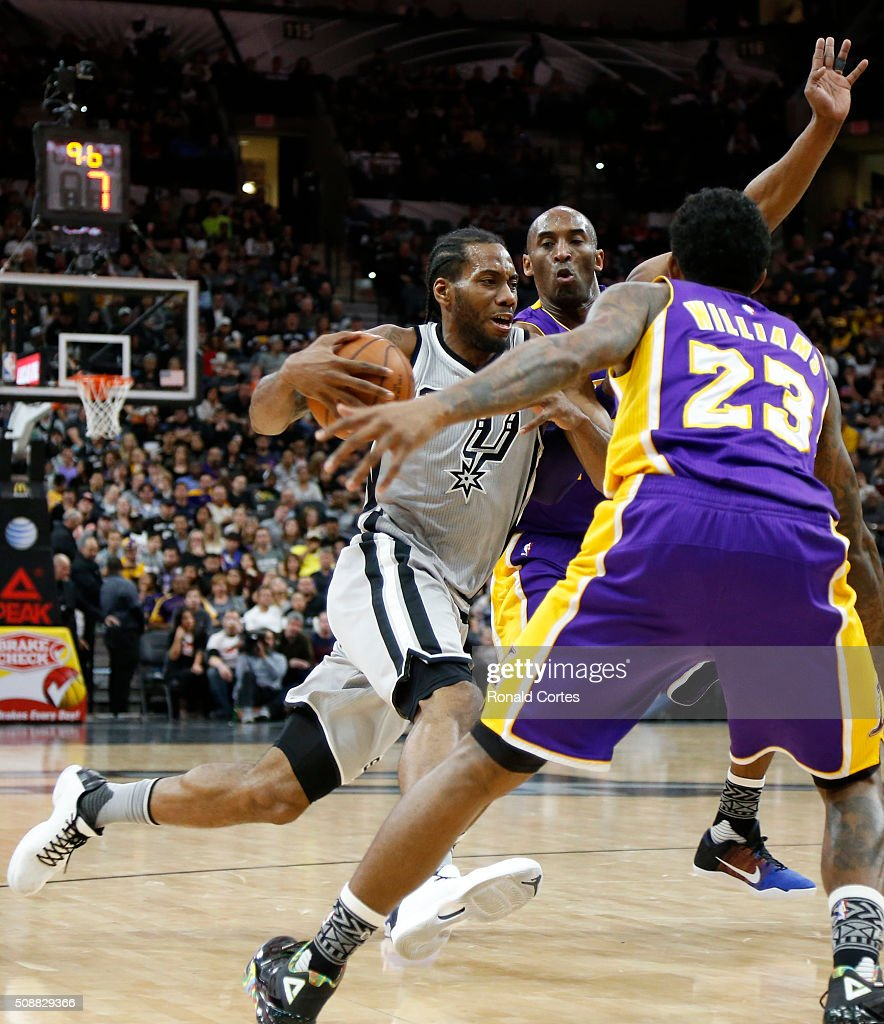 Kawhi Leonard #2 of the San Antonio Spurs drives on Kobe Bryant #24 of the Los Angeles Lakers at AT&T Center on February 6, 2016 in San Antonio, Texas.