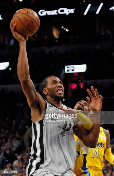 Kawhi Leonard of the San Antonio Spurs drives past Will Barton of the Denver Nuggets at ATT Center on January 13 2018 in San Antonio Texas NOTE TO...