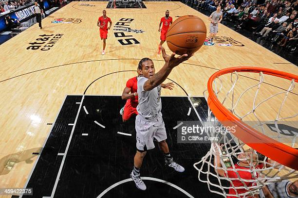 Kawhi Leonard of the San Antonio Spurs drives to the basket against the Houston Rockets during the game at the ATT Center on December 25 2013 in San...