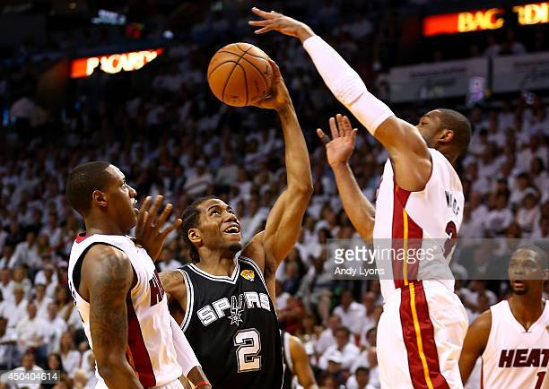 Kawhi Leonard of the San Antonio Spurs goes to the basket against Dwyane Wade of the Miami Heat during Game Three of the 2014 NBA Finals at American...