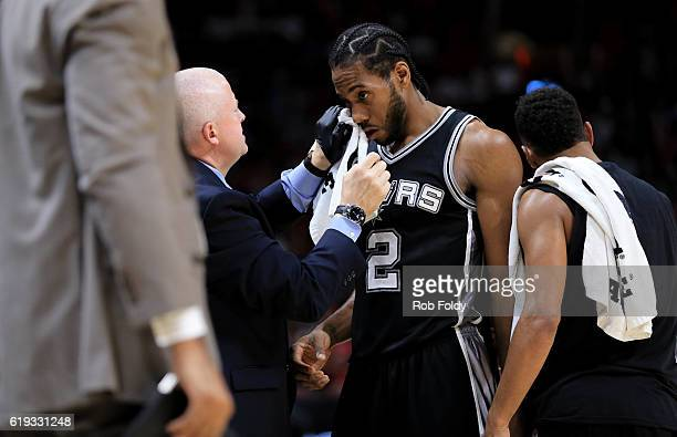 Kawhi Leonard of the San Antonio Spurs is tended to by a trainer for a cut under his eye during the fourth quarter of the game against the Miami Heat...
