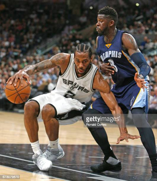 Kawhi Leonard of the San Antonio Spurs loses his balance as he is guarded by James Ennis III of the Memphis Grizzlies in Game Five of the Western...