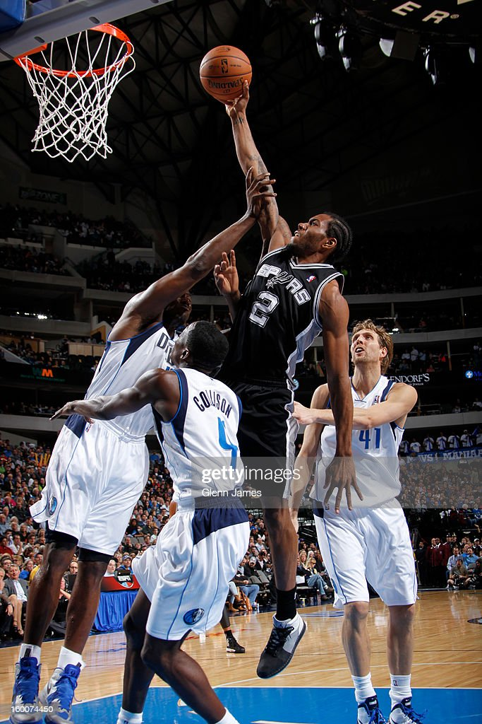 Kawhi Leonard #2 of the San Antonio Spurs puts in the layup against Darren Collison #4 of the Dallas Mavericks on January 25, 2013 at the American Airlines Center in Dallas, Texas.