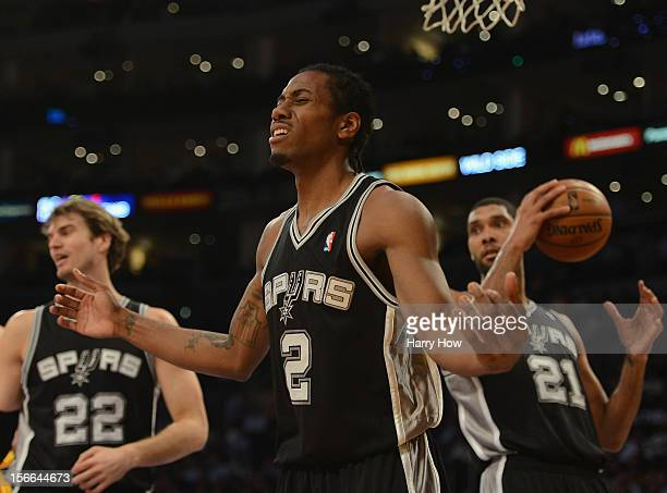 Kawhi Leonard of the San Antonio Spurs reacts to his charginfg foul in front of teammates Tiago Splitter and Tim Duncan during the game against the...