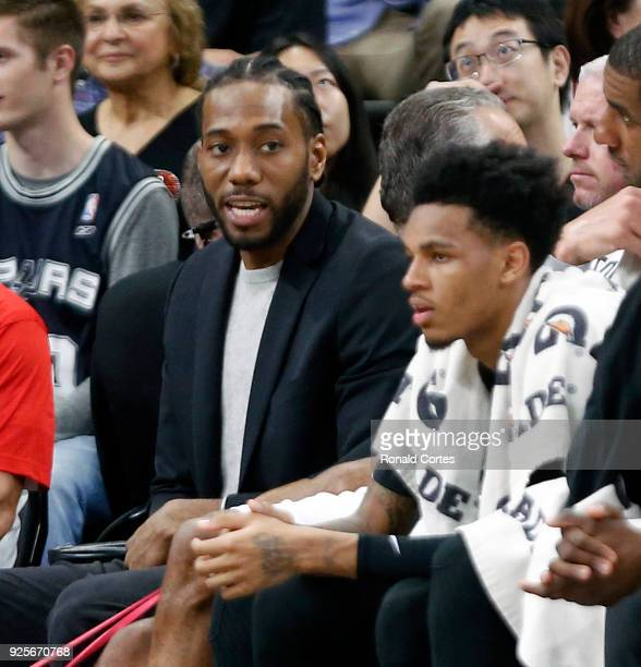 Kawhi Leonard of the San Antonio Spurs sits on the bench in street clothes during a game against the New Orleans Pelicans at ATT Center on February...