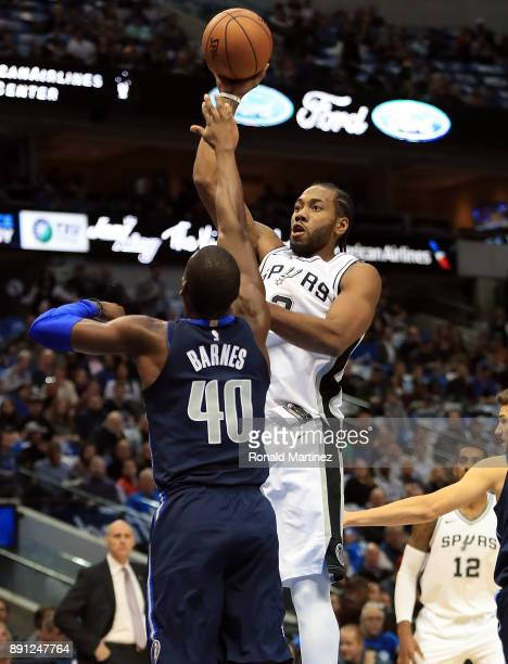 Kawhi Leonard of the San Antonio Spurs takes a shot against Harrison Barnes of the Dallas Mavericks at American Airlines Center on December 12 2017...
