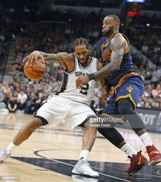 Kawhi Leonard of the San Antonio Spurs tries to drive on LeBron James of the Cleveland Cavaliers at ATT Center on March 27 2017 in San Antonio Texas...