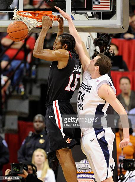 Kawhi Leonard of the San Diego State Aztecs dunks in front of Noah Hartsock of the Brigham Young University Cougars during the championship game of...