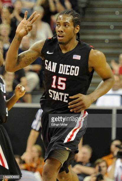 Kawhi Leonard of the San Diego State Aztecs holds up three fingers after scoring a threepoint basket against the Brigham Young University Cougars...