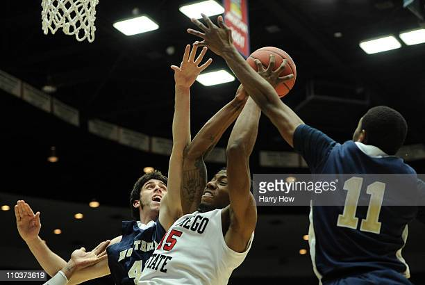 Kawhi Leonard of the San Diego State Aztecs shoots against Elliott Lloyd and Mike Proctor of the Northern Colorado Bears during the second round of...