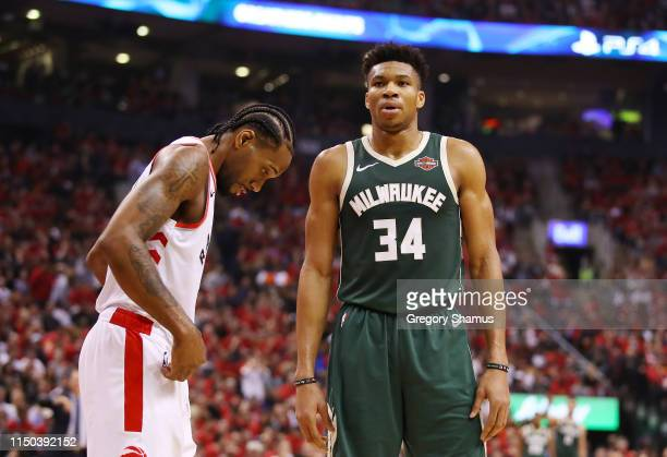Kawhi Leonard of the Toronto Raptors and Giannis Antetokounmpo of the Milwaukee Bucks react during the first half in game three of the NBA Eastern...