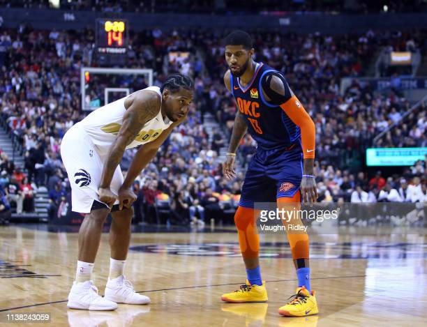 Kawhi Leonard of the Toronto Raptors and Paul George of the Oklahoma City Thunder prepare for play to resume during the second half of an NBA game at...