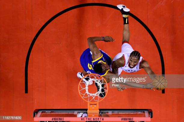 Kawhi Leonard of the Toronto Raptors attempts a shot against Kevon Looney of the Golden State Warriors in the second half at Scotiabank Arena on May...
